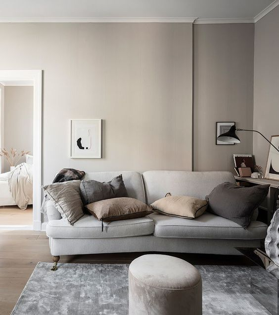 a relaxing greige living room with a grey sofa, muted color pillows, a bookshelf, some artworks and a black table lamp