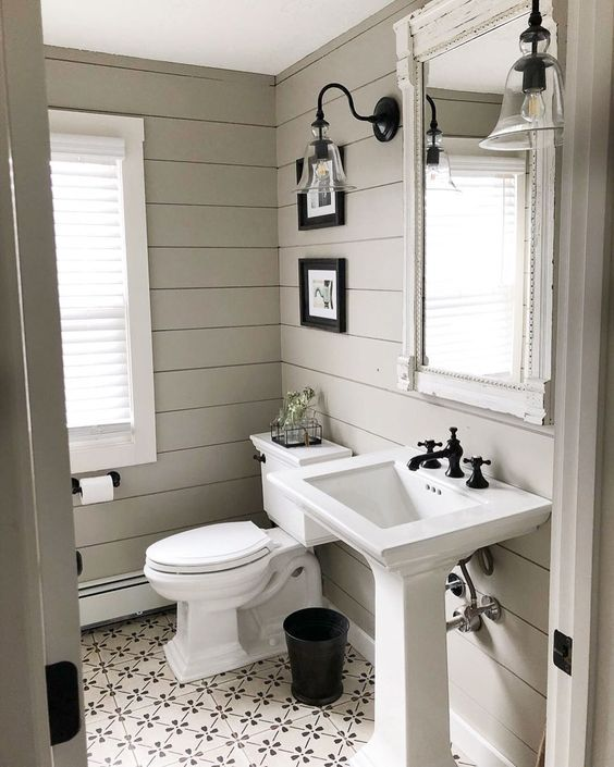 a rustic greige bathroom with planked walls and tiles on the floor, a free-standing sink and white appliances, a vintage mirror and sconces