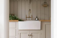 a rustic greige kitchen with shaker cabinets, a matching planked wood backsplash, butcherblock countertops and touches of brass