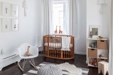 a serene Scandi nursery with a rich-stained crib and all the rest done in grey and white, with a grid gallery wall and some lovely toys