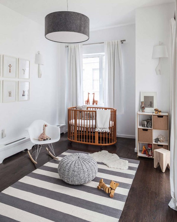 a serene Scandi nursery with a rich stained crib and all the rest done in grey and white, with a grid gallery wall and some lovely toys