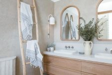 a serene and welcoming greige bathroom with a light-stained floating vanity, a ladder, arched windows in wooden frames and a cool sconce