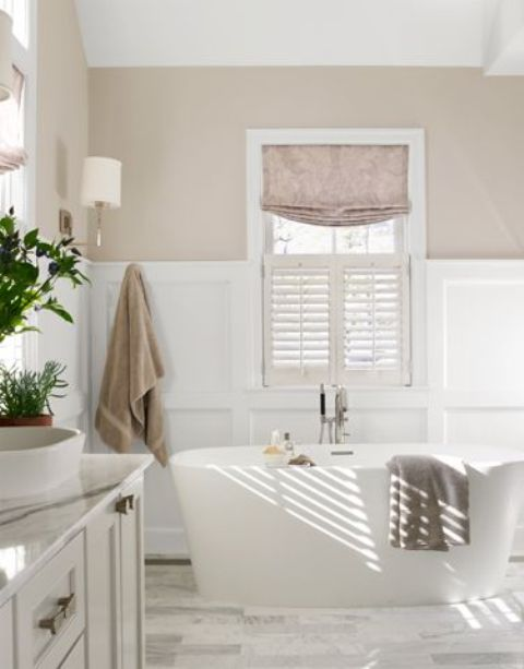 a serene bathroom with greige and white paneling walls, a white stone tile floor, an oval tub, a white vanity with a bowl sink and potted plants