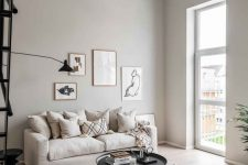 a serene greige living room with a neutral sofa, a round black coffee table and a side one, printed pillows and a small gallery wall