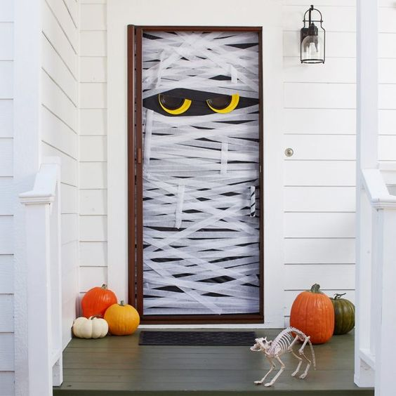 a simple Halloween front door styled as a mummy with eyes, with colorful pumpkins and a cat skeleton is a fun and easy DIY idea