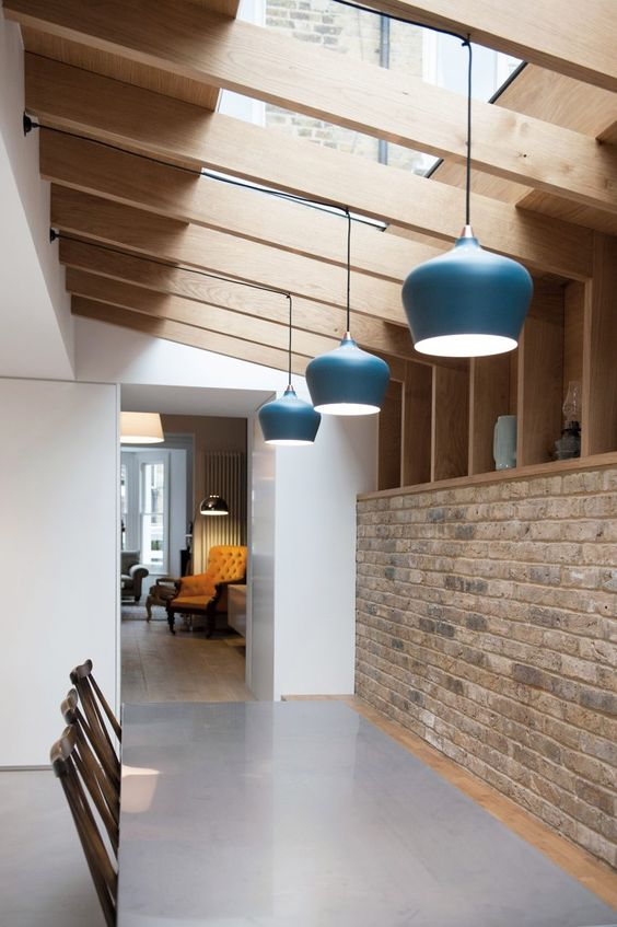 a simple and laconic dining space with a brick wall and open storage shelves, wooden beams and pendant lamps, a dining set lit up with skylights
