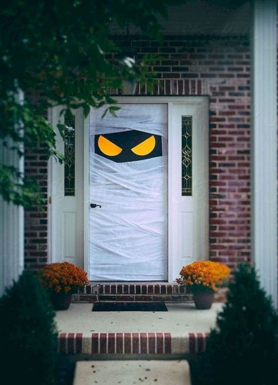 a simple and stylish mummy front door plus bold blooms in planters are amazing for styling your front porch for Halloween
