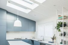 a sleek and plain blue ktichen with white countertops and a white backsplash, a series of skylights that illuminates the space