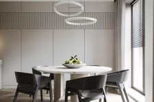 a sleek and refined minimalist dining room with greige walls, a round table, black chairs, round chandeliers and natural light