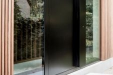 a sleek black metal front door and windows on both side of it is a cool idea for a modern or contemporary house, and will fit a minimalist one, too