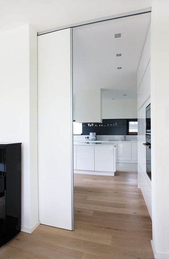 a sleek white pocket door is a cool and minimalist way to separate the spaces without spoiling any interior and look