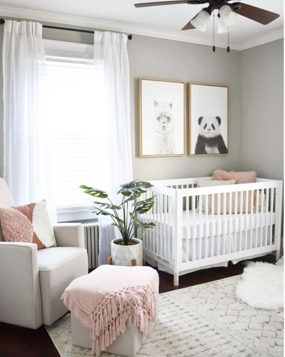 a small contemporary Scandi nursery with grey walls, white and creamy furniture, a printed rug, pink touches and a couple of prints on the wall