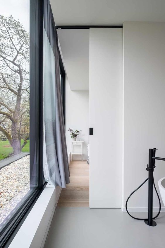 a small and delicate white pocket door with a black handle is a cool idea to hide a bathroom in a bedroom and looks cool