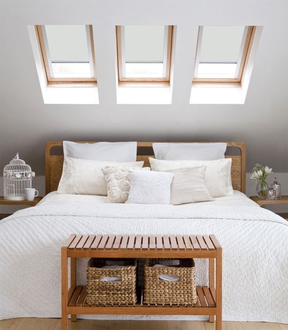 a small attic space with three skylights instead of a headboard is a nice idea to get natural light and visually enlarge the space