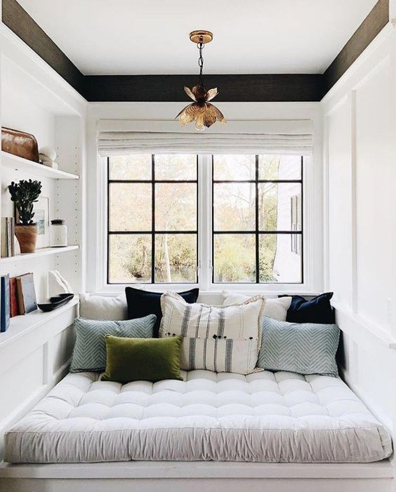 a small contemporary reading nook by the window, with some shelves built in and colorful pillows