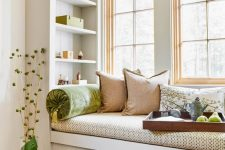 a small windowsill reading nook with bright pillows and built-in shelves looks super cozy and fresh and welcomes you to read