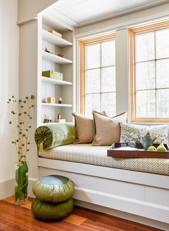 a small windowsill reading nook with bright pillows and built in shelves looks super cozy and fresh and welcomes you to read
