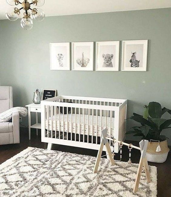 a soothing Scandi nursery with pale green walls, a white crib, a mini gallery wall, a potted plant, a neutral chair and a nightstand