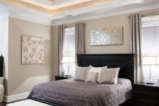a sophisticated greige bedroom with black furniture, a white upholstered bed, bold artworks and a double-height ceiling is amazing
