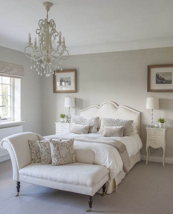 a sophisticated greige bedroom with creamy seating furniture and nightstands, an elegant white chandelier and small artworks