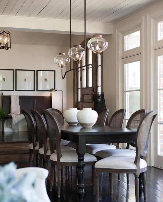 a sophisticated greige dining room with a green sofa, a black dining table, black and white chairs, a chic chandelier and a grid gallery wall