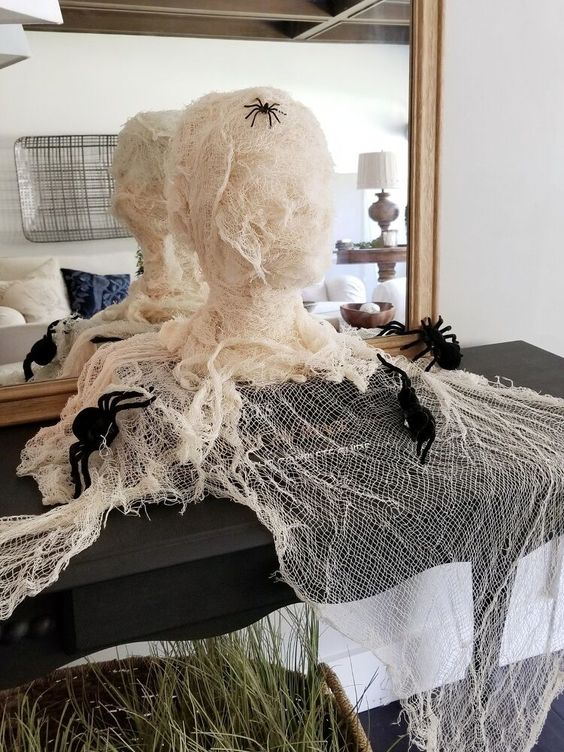 a spooky mummy head with spiders is a lovely decoraiton for Halloween that you can easily make yourself