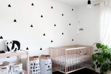a stylish Nordic nursery with an accent wall, stained furniture, a pendant bulb, some toys and a potted plant is a lovely space