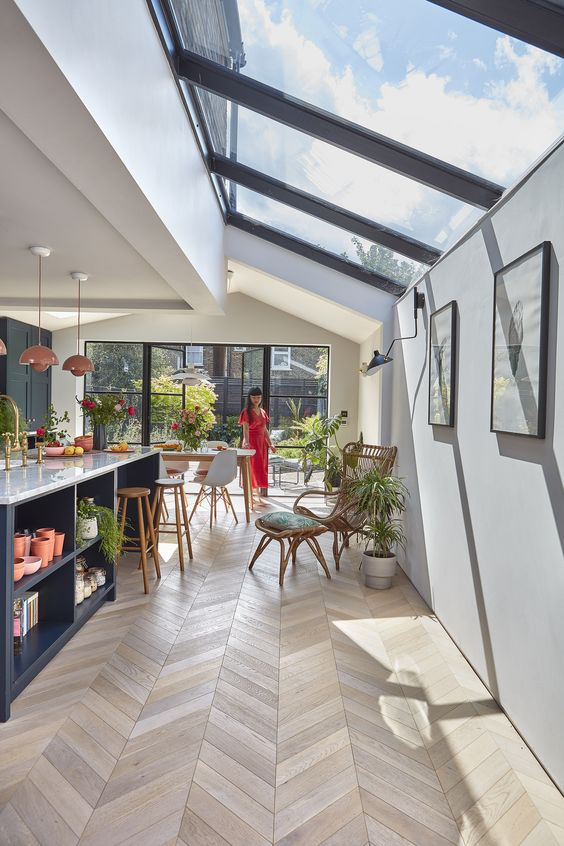 a stylish and chic space with a kitchen and a dining room, with a glazed wall and a series of skylights that cozy up the space