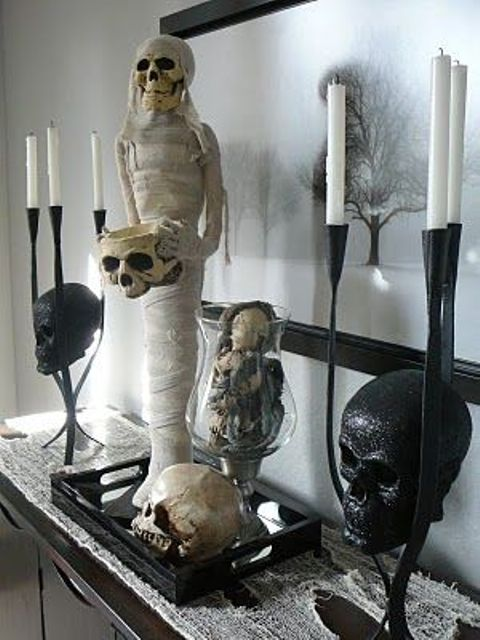 a stylish and scary Halloween decoration of a mummy, skulls and bones on a tray is a gorgeous idea to go for