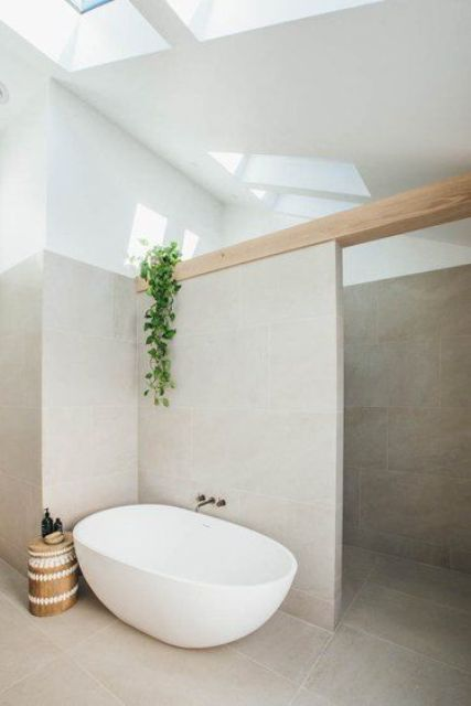 a stylish greige bathroom clad with large scale tiles, a wooden beam, a shower space, an oval tub an a wooden side table plus skylights