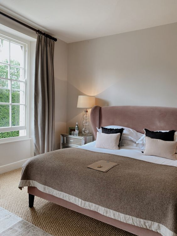 a stylish greige bedroom with a dusty pink velvet bed, neutral and blush bedding, mirrored nightstands, grey curtains and a jute rug