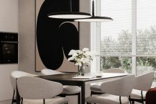 a stylish greige dining room with a black table, neutral chairs, black pendant lamps, a statement artwork and a burgundy sofa is wow