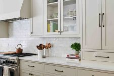 a stylish greige kitchen with white stone countertops, a white subway tile backsplash and black fixtures is chic and cool