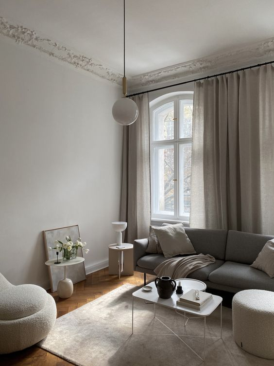 a stylish greige liivng room with a grey sofa, neutral seating furniture, a lightweight coffee table, some pendant and usual lamps