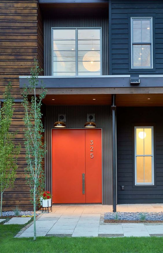 a stylish modern orange metal front door with a house number is an ultimate solution for a mid-century modern house