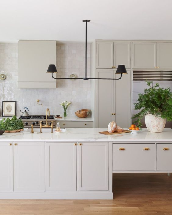 a subtle greige kitchen with shaker cabinets, a catchy kitchen island, a black chandelier, a glossy tile backsplash and white stone countertops