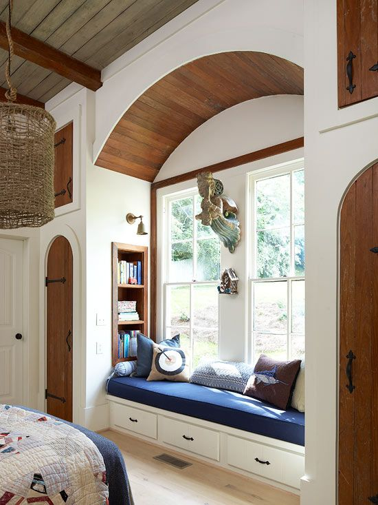 a traditional windowsill reading space with an upholstered bench with drawers and built in stained bookshelves