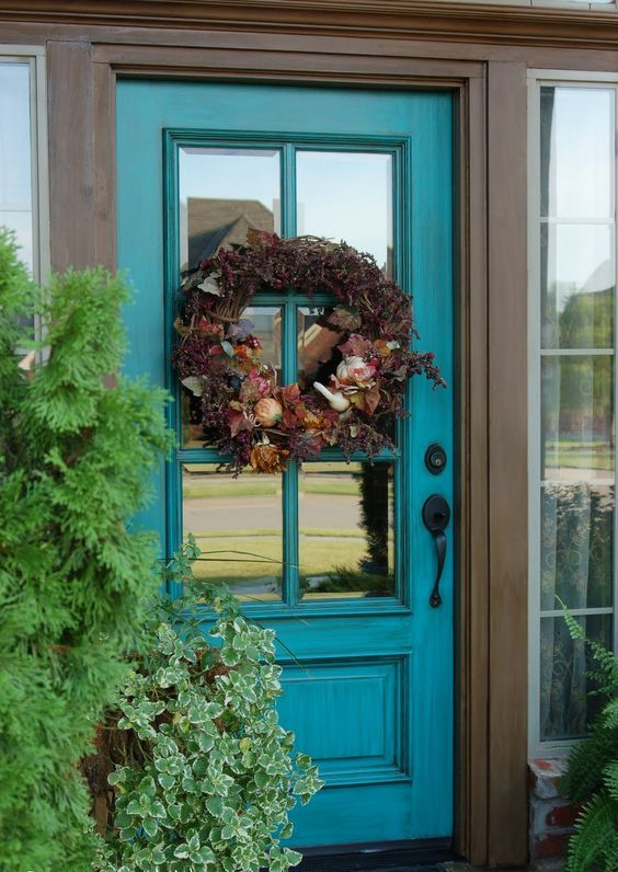 a turquoise glass front door is a refined idea that brings color and looks very chic and stylish, ideal for a refined house