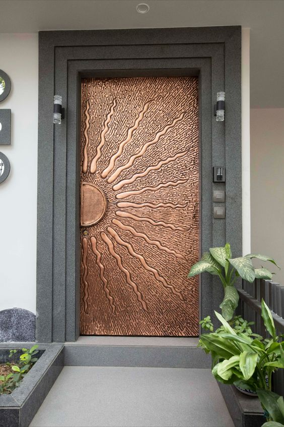 a unique copper door with a sun portrayed is a gorgeous idea to make a statement with its color and this image