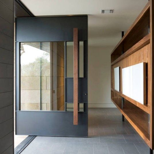 a unique oversized blackened metal front door with a large window right in its center and a wooden handle is gorgeous