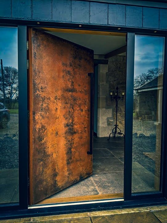 a unique weathered oversized metal front door with an oversized handle is a fantastic solution with an unusual color scheme