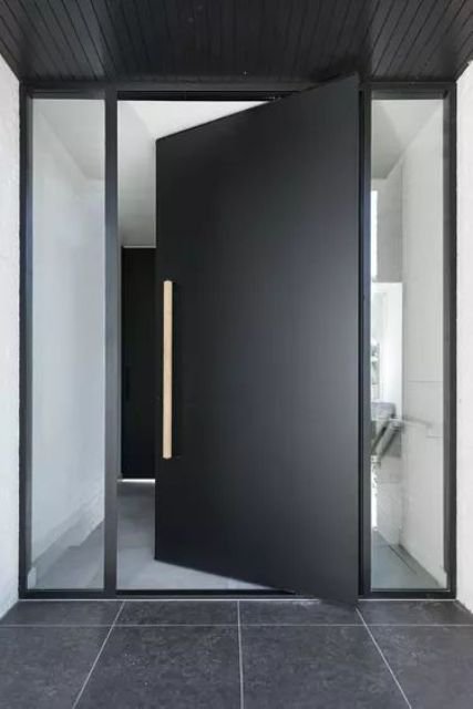 a very laconic and stylish matte black metal front door with a handle and long and narrow windows on each side is amazing