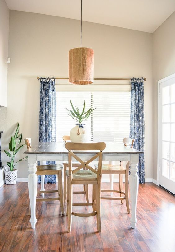a very simple and relaxed greige dining space with a dining table and stained chairs, blue printed curtains, a pendant lamp