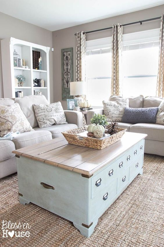 a vintage farmhouse greige living room with neutral sofas, a blue chest coffee table, an open storage bookcase, printed textiles
