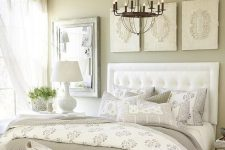 a vintage greige bedroom with a white upholstered bed, a white upholstered bench, a pretty gallery wall, some printed yet neutral bedding and textiles