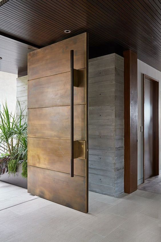 a weathered oversized metal front door with an oversized handle is a cool idea for a modern house and it makes a statement