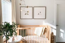 a welcoming Scandi nursery with stained furniture, a printed rug, a couple of artworks and a mobile, a basket for storage and a potted plant