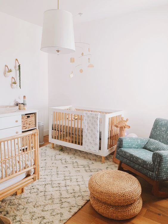 a welcoming Scandi nursery with white and stained furniture, a blue rocker chair, jute poufs, a white dresser and a pendant lamp