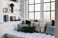 a welcoming and cozy reading nook by the window – a soft upholstered seat with drawers and some built-in shelves right here