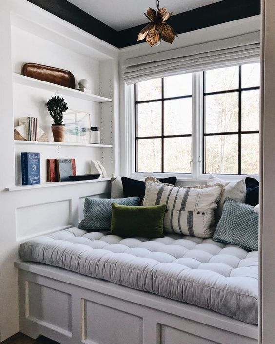 a welcoming and cozy reading nook by the window   a soft upholstered seat with drawers and some built in shelves right here